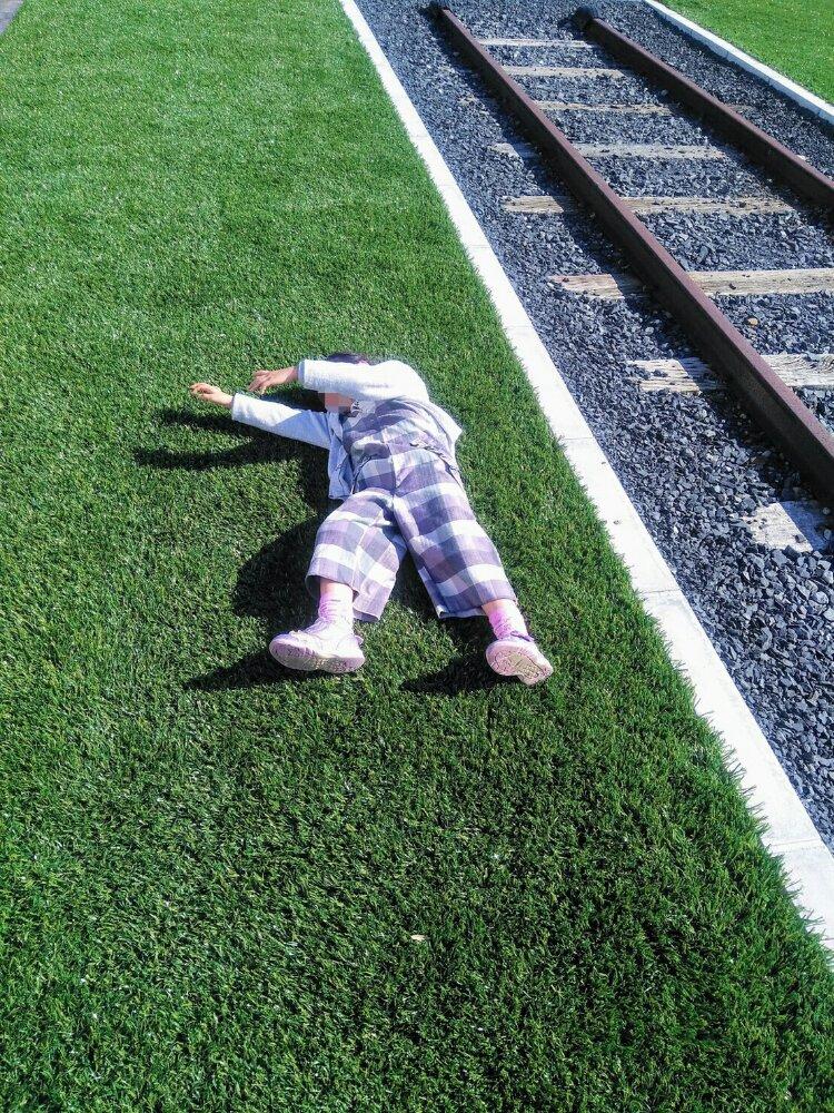 線路わきに寝そべる子供